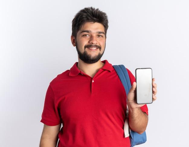 白い背景の上に元気に立って笑顔のスマートフォンを示すバックパックと赤いポロシャツの幸せな若いひげを生やした学生の男
