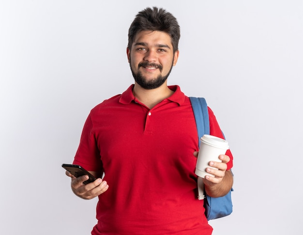 Felice giovane studente barbuto in polo rossa con zaino che tiene in mano una tazza di caffè e uno smartphone che sorride allegramente in piedi sul muro bianco