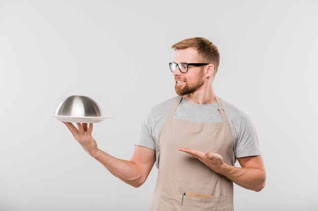 Happy young bearded waiter of cafe in apron and eyeglasses showing cloche with prepared food in isolation