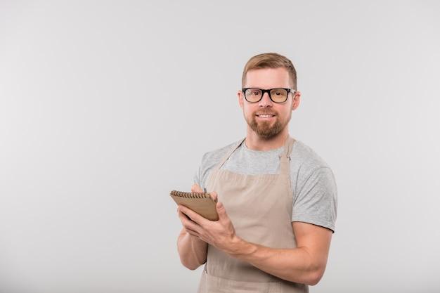 Счастливый молодой бородатый официант в фартуке и очках записывает заказ клиента в блокноте перед камерой изолированно
