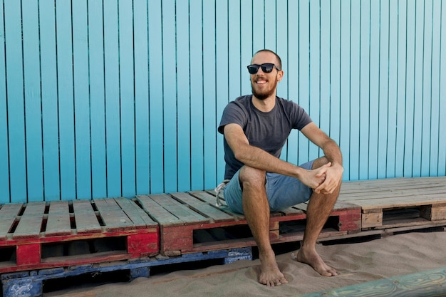 Счастливый молодой бородатый в солнцезащитных очках улыбается на пляже исла канела, сидя перед деревянной синей стеной, глядя в сторону