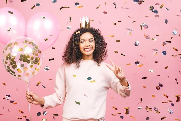 カラフルなパーティー風船と紙吹雪とピンクのtシャツと幸せな若い美しいアフリカ系アメリカ人女性