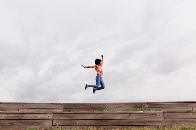 Счастливая молодая красивая афро американская женщина слушая к музыке в ее мобильном телефоне и скача. облачный фон. весна или лето. повседневная одежда