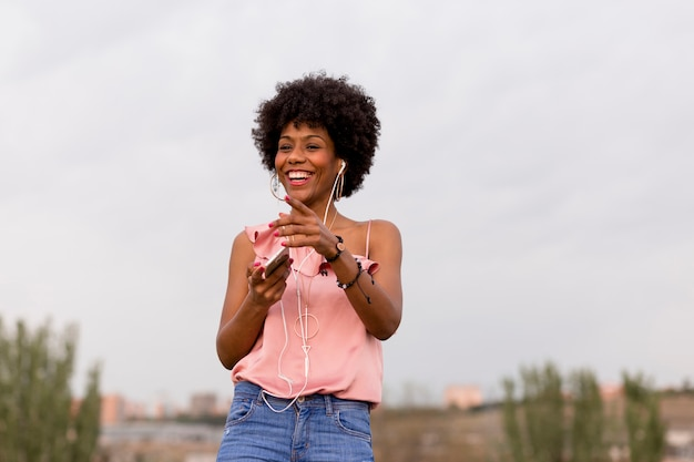 Счастливая молодая красивая афро американская женщина слушая к музыке на ее мобильном телефоне и усмехаться. городской фон. весна или лето. повседневная одежда.