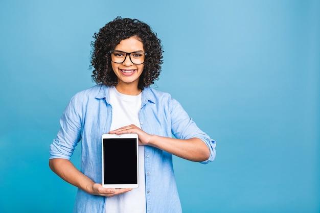 파란색 배경 위에 절연 빈 태블릿 컴퓨터를 보여주는 행복 한 젊은 아름 다운 아프리카 미국 여자.