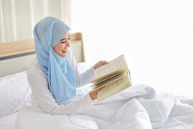 Счастливая молодая красивая азиатская арабская женщина в пижаме сидит