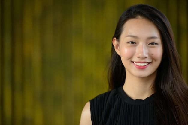 대나무 울타리에 대 한 행복 한 젊은 아름 다운 아시아 사업가