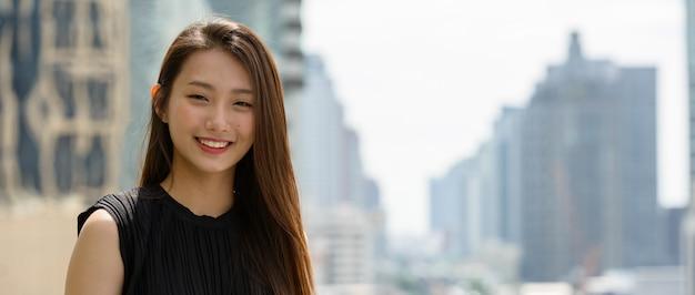 도시의 전망에 대 한 행복 한 젊은 아름 다운 아시아 사업가