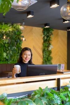 コーヒーショップでノートパソコンを使用しながらコーヒーを保持している幸せな若い美しいアジア女性実業家