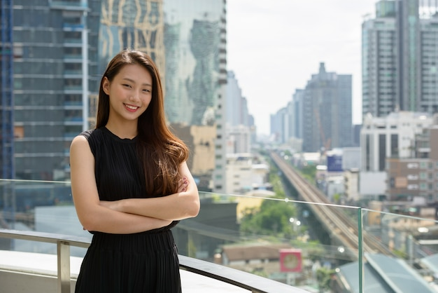 Happy young beautiful asian businesswoman smiling with arms crossed against view of the city