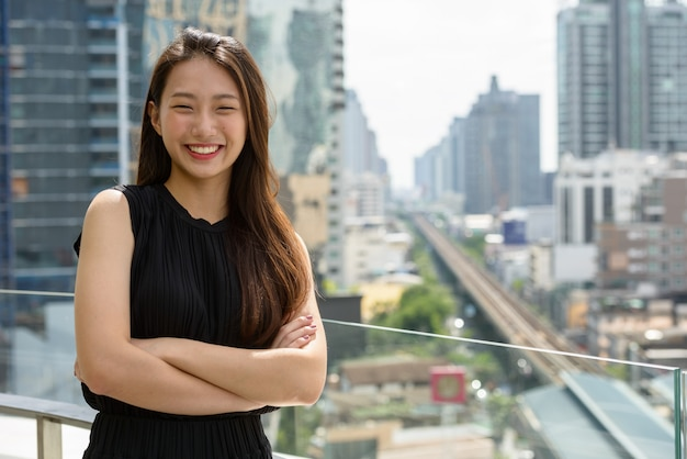 팔 웃고 행복 젊은 아름 다운 아시아 사업가 도시의 전망을 넘어