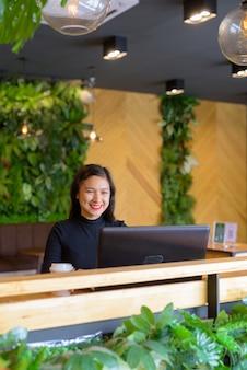 コーヒーショップでラップトップを使用して幸せな若い美しいアジア女性実業家