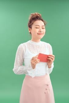 緑の背景に愛のはがきバレンタインと幸せな若い美しいアジアの女の子