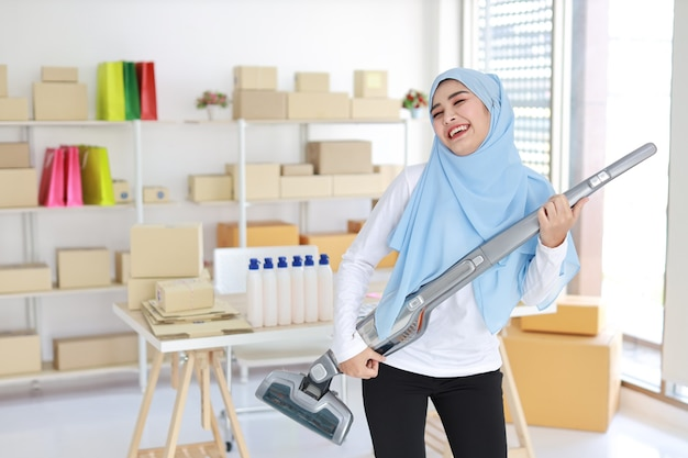 Happy young beautiful asian muslim housewife woman cleaning and playing vacuum cleaning like guitar