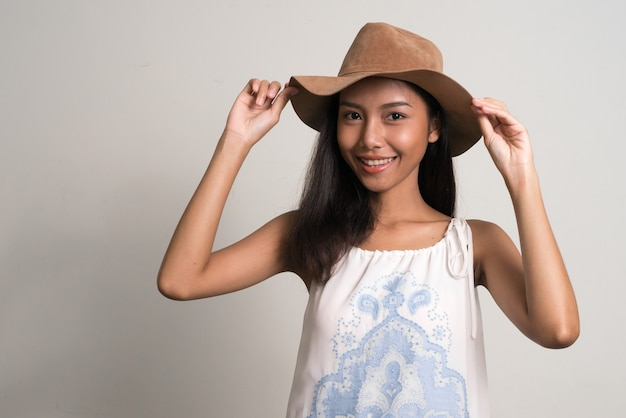 Happy young beautiful asian teenage girl as tourist holding hat