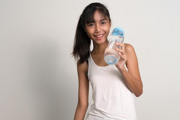Happy young beautiful asian teenage girl holding water bottle