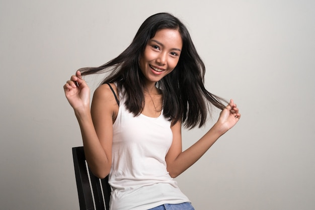 Happy young beautiful asian teenage girl sitting and smiling