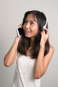 Happy young beautiful asian teenage girl thinking and listening to music
