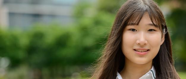 공원에서 행복 한 젊은 아름 다운 아시아 십 대 여자