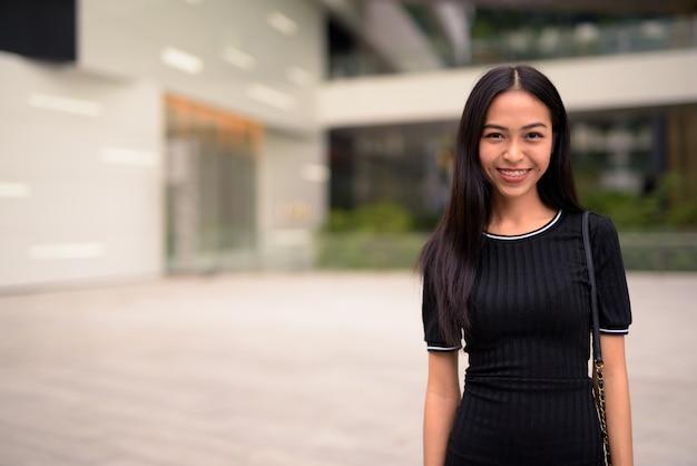 屋外のモールで幸せな若い美しいアジア観光女性