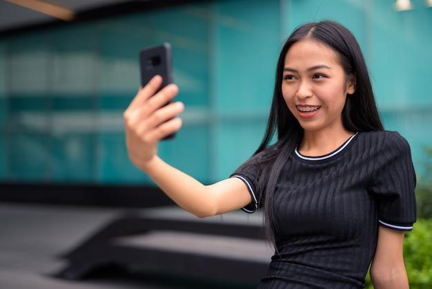 屋外のモールでselfieを取って幸せな若い美しいアジア観光女性