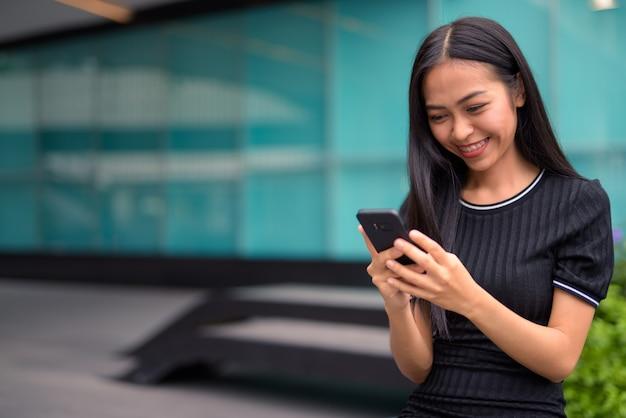 屋外のモールで電話を使用して幸せな若い美しいアジア観光女性