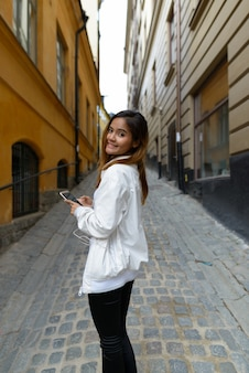 스웨덴의 빈티지 건물 골목에서 전화와 함께 행복 한 젊은 아름 다운 아시아 관광 여자