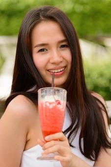 屋外のコーヒーショップでミルクセーキを飲む幸せな若い美しいアジアの女性