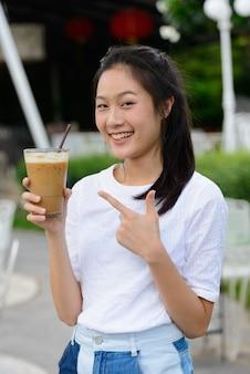 屋外の喫茶店でコーヒーを保持している幸せな若い美しいアジアの女性