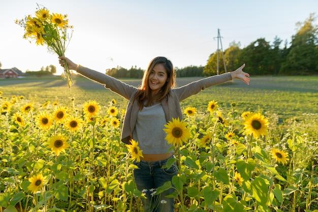 ひまわりの庭の農場で両手を広げて花を持って幸せな若い美しいアジアの女性