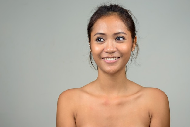 Счастливая молодая красивая азиатская женщина без рубашки как концепция здоровья и красоты