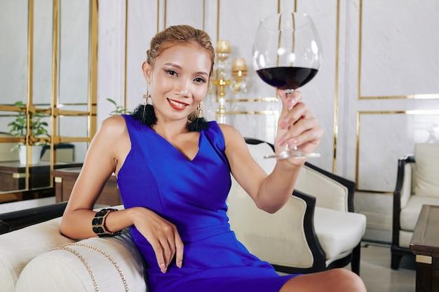 椅子に座って赤ワインのグラスでポーズをとって幸せな若い美しいアジアの女性