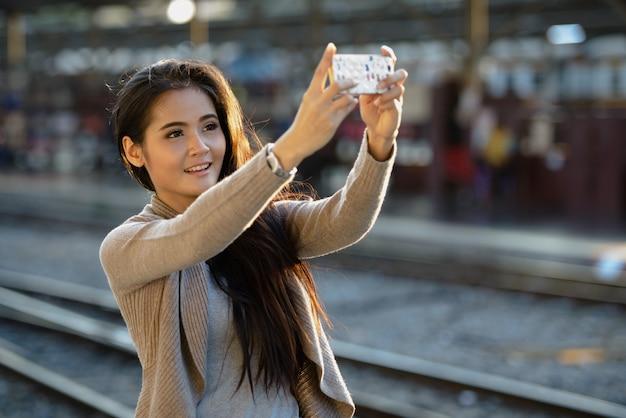 기차역에서 셀카를 복용 행복 젊은 아름 다운 아시아 여자