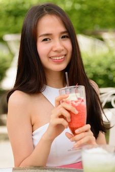 屋外のコーヒーショップでミルクセーキと幸せな若い美しいアジアの女性