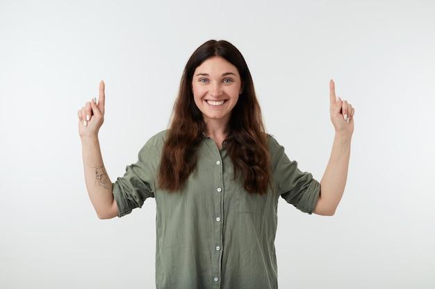 彼女の人差し指を維持する自然なメイクで幸せな若い美しい茶色の髪の女性