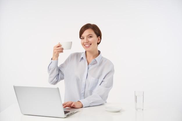 お茶と手を上げて、白い上に座って、魅力的な笑顔で元気に見えるナチュラルメイクで幸せな若い美しい茶色の髪の女性