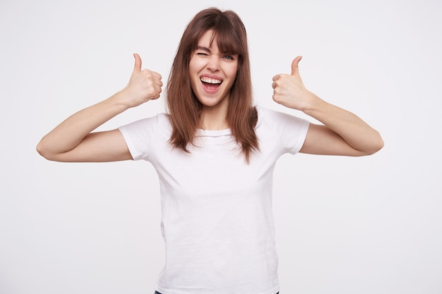 Happy young beautiful brunette woman with casual hairstyle showing raised thumbs while looking cheerfully  and giving wink, isolated over white wall