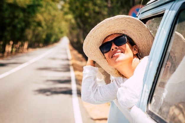 幸せな若い美しい白人女性は青い古い車の窓の外で太陽を楽しむ