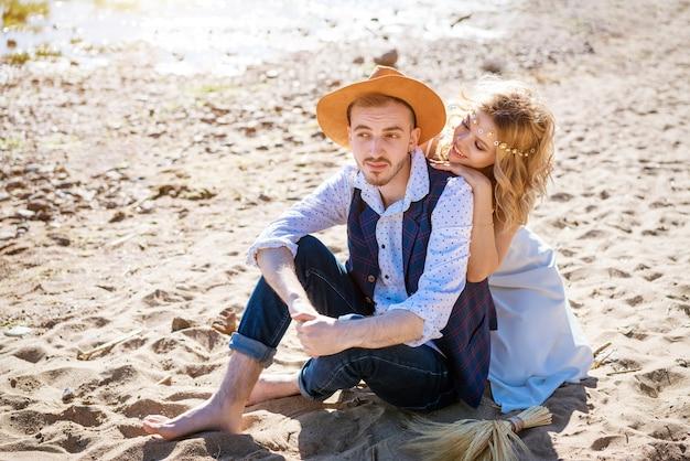 Счастливая молодая красивая пара оружия на пляже в солнечный день. концепция взаимоотношений