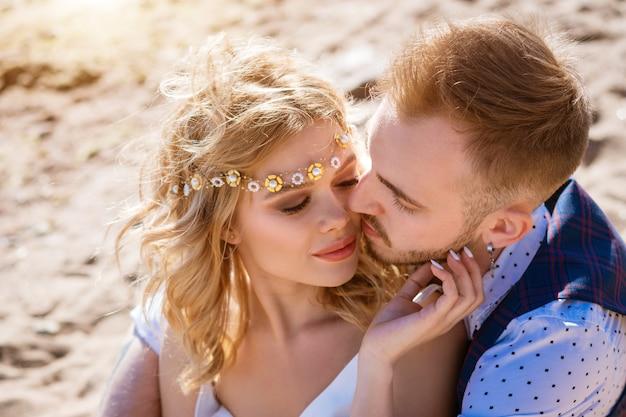 Счастливая молодая красивая пара в руках на пляже
