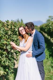 Счастливая молодая красивая пара в синей одежде, прогулки в саду в солнечный день. пара в любви, улыбаясь, обниматься и целоваться на фоне прекрасного виноградника в италии