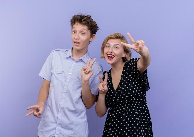 행복 한 젊은 아름 다운 커플 남자와 여자는 파란색 벽 위에 서 승리 표지판을 보여주는 웃 고
