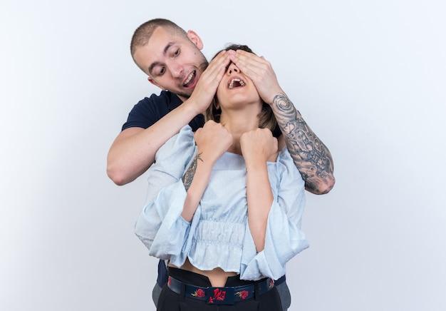 白い壁に彼女の目を覆っている彼のガール フレンドの後ろに立っている幸せな若い美しいカップルの男