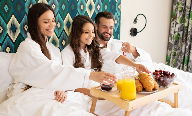 Happy young beautiful family in bathrobes are taking morning breakfast in a luxury hotel room