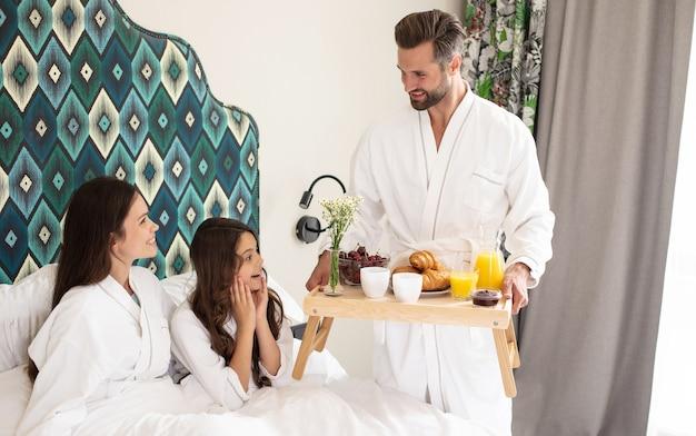 Счастливая молодая красивая семья в халатах принимает утренний завтрак в роскошном гостиничном номере