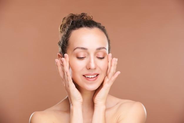 幸せな若い美しい女性が指で顔をマッサージし、朝の衛生状態の後に隔離された手順を楽しんでいます