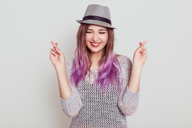 Happy young beautiful female wearing shirt and hat crossing fingers, hopes for something good, keeps eyes closed and has toothy smile, isolated over white wall.