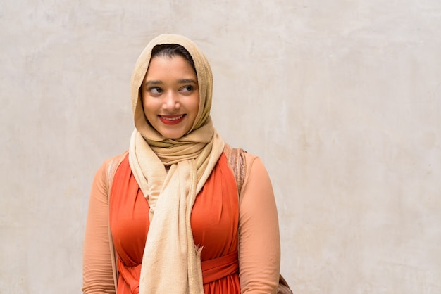 Happy young beautiful indian muslim woman thinking against concrete wall