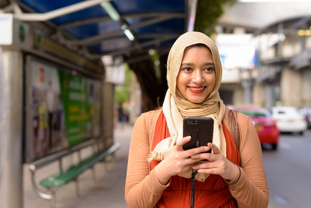 Happy young beautiful indian muslim woman thinking while using phone at the bus stop