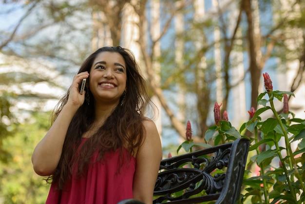 Счастливая молодая красивая индийская женщина разговаривает по телефону в парке